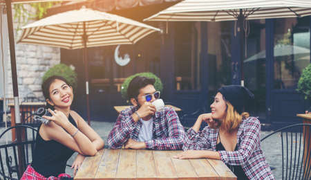 ingram: Group of young hipster sitting in a cafe,Young cheerful friends having fun while take time together, Holiday freedom enjoy.