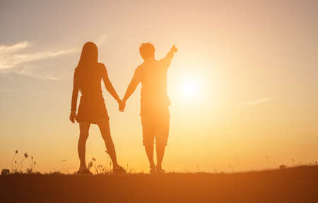 silhouette of a man and woman holding hands with each other, walking together. Stock Photo