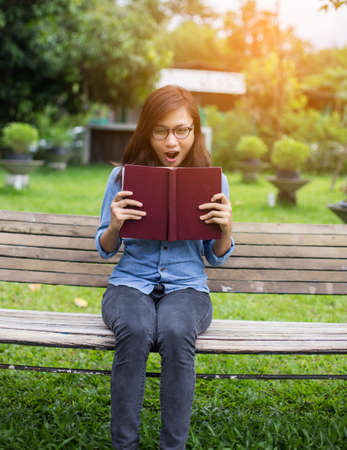 A woman sitting in the garden reading a book.