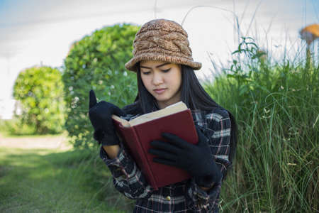 good weather: Hipster charming girl relaxing in the park while read book, Enjoy nature around.