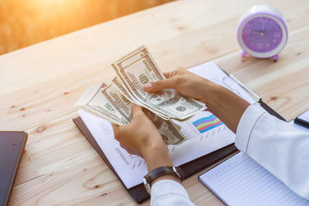 bens: Business woman gripping The United States hundred-dollar bills in her hand and some put on the table full with business charts and notebook
