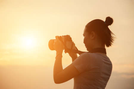 silhouette photographer woman in the sunset Stock Photo