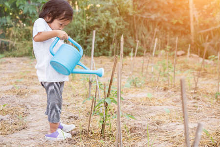 Little girl watering tree with watering pot