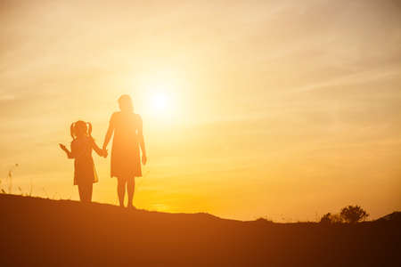 Mother encouraged her daughter out of the shadows at sunset.