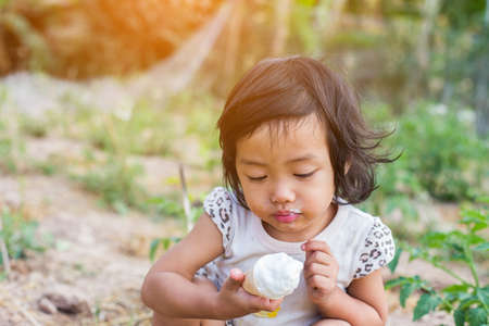 Little curly girl with ice cream on colorful background Stock Photo