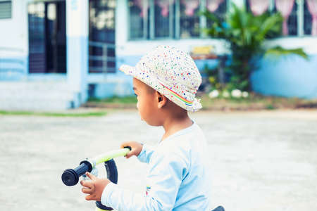 A cute kid riding a bicycle Imagens