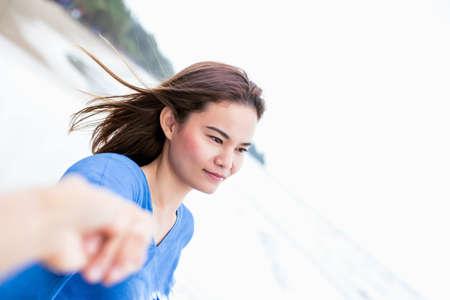 Asiatische Männer und Frauen schütteln sich am Strand die Hand