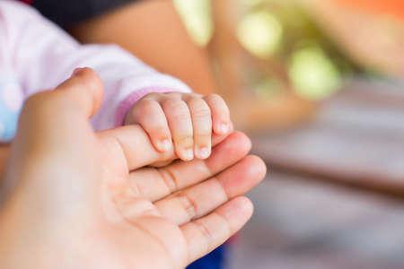 Kleines neugeborenes Baby in der großen Hand der Mutter.