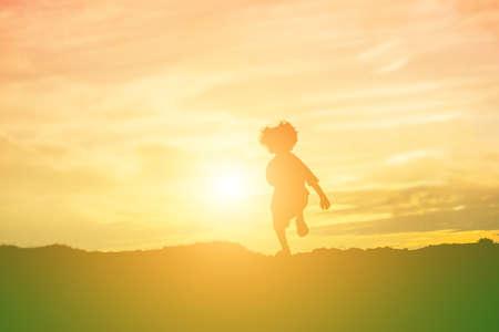 silueta de niño, Momentos de alegría del niño. En el atardecer de la naturaleza