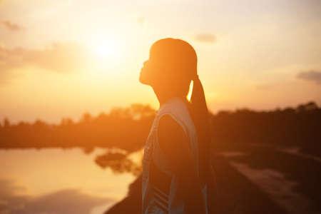 silna pewność siebie kobieta otwartymi ramionami pod zachodem słońca. Zdjęcie Seryjne