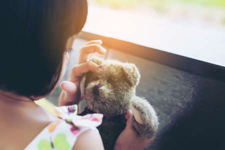 Little child girl is reading a book in evening in dark with a toy bear stock photo Stock Photo