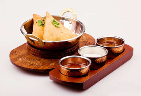 oryginal: delicious Indian food in traditional wooden plate with sauces