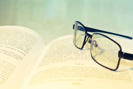 Closeup of opened book and glasses Foto de archivo