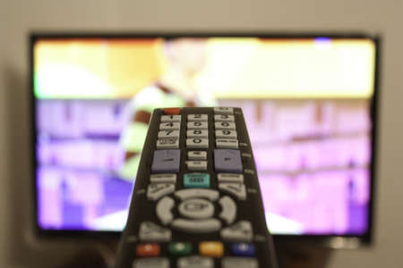 sports programme: TV remote in a living room Stock Photo