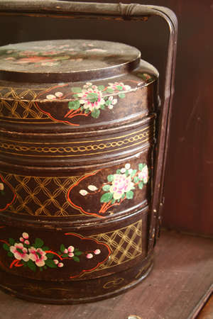 tiffin: close up of traditional three storey tiffin carrier painted with flower motifs