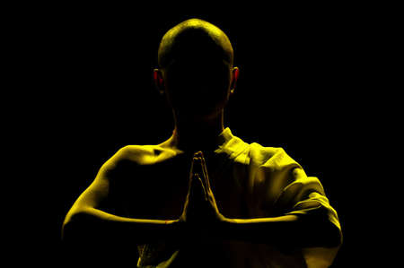 silhouette of monk praying in lotus position