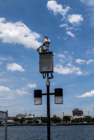 cctv and light poles on blue sky photo