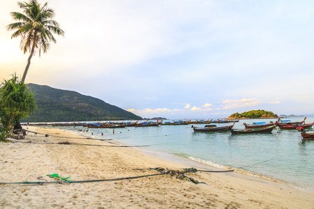 long tailed boat: Long tailed boat on beach with white sand  and mountains Editorial