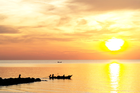 romantic background: Sunrise on the beach with fishing boat in the morning Stock Photo