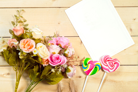 white card: Roses flowers and empty tag for your text with heart-shaped candy on wooden background