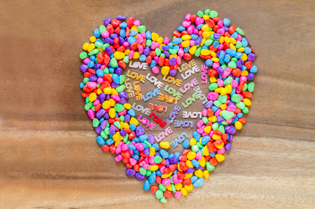 heart shaped stuff: Word Love with Heart shaped Valentines Day  with stones color abstract on wood background