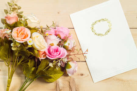 text pink: Roses flowers and empty tag for your text on wooden background