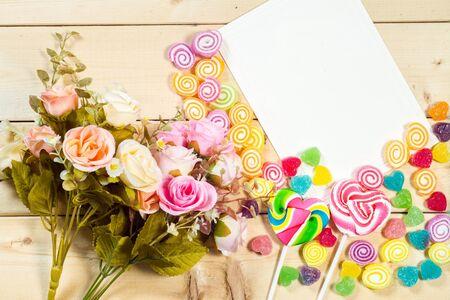 Rozen bloemen en lege tag voor uw tekst met hart-vormige snoep op houten achtergrond