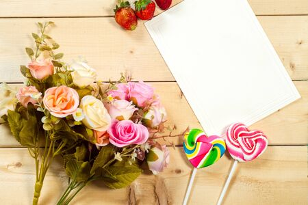 valentine card: Roses flowers and empty tag for your text with heart-shaped candy on wooden background