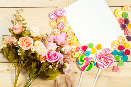 felicitaciones cumplea�os: Roses flowers and empty tag for your text with heart-shaped candy on wooden background