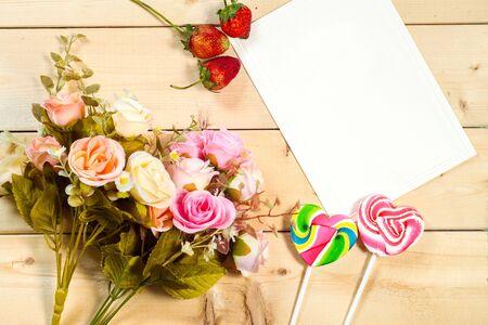 felicitaciones cumplea�os: Rosas flores y etiqueta vac�a para el texto con el caramelo en forma de coraz�n sobre fondo de madera