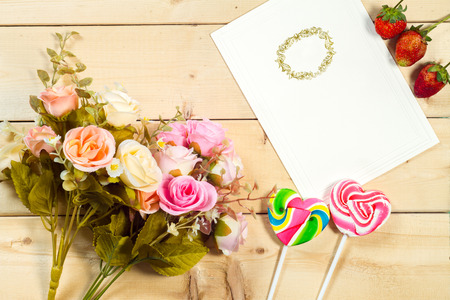 text pink: Roses flowers and empty tag for your text with heart-shaped candy on wooden background