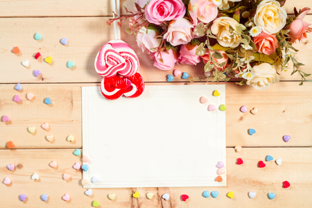 felicitaciones de cumplea�os: Pastel color tone  roses flowers and empty tag for your text with heart shape candy on wooden background