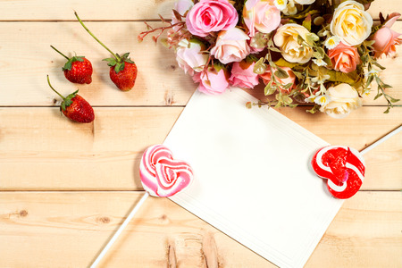 birthday greetings: Pastel color tone  roses flowers and empty tag for your text with heart shape candy on wooden background