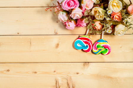 birthday greetings: Roses flowers  with heart shape candy on wooden background Pastel color tone
