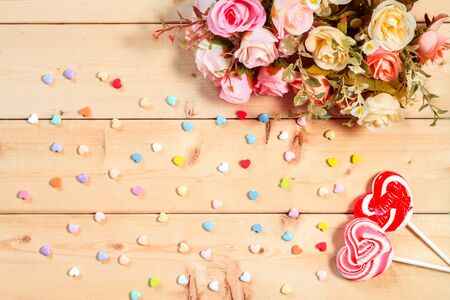 text pink: Roses flowers  with heart shape candy on wooden background Pastel color tone