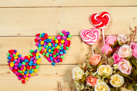 fond de texte: Roses flowers  with heart shape candy on wooden background Pastel color tone