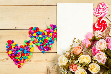text pink: Pastel color tone  roses flowers and empty tag for your text with heart shape candy on wooden background