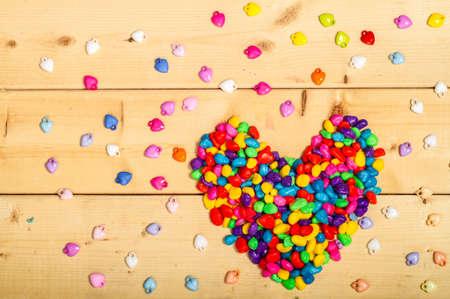 felicitaciones cumplea�os: la forma del coraz�n de colores en el fondo de madera Foto de archivo