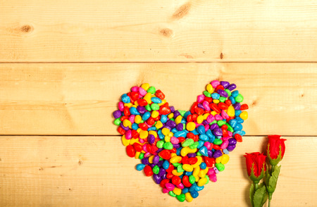 birthday greetings: Red roses flowers with heart shape colorful on wooden background