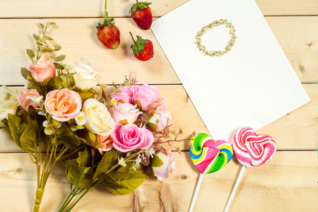 blank card: Roses flowers and empty tag for your text with heart-shaped candy on wooden background