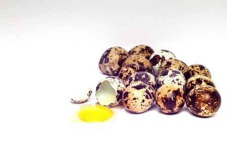 quail eggs cracked on white background Stock Photo