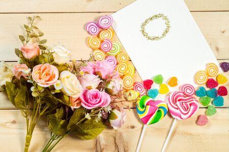 Roses fleurs et vide tag pour votre texte avec des bonbons en forme de coeur sur fond de bois
