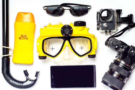 summer on beach had yellow and black diving mask and sunblock with camera on a white background