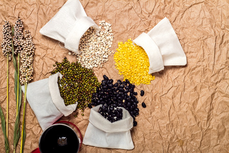 brown paper background: Mixed beans in sack on brown paper background, mung bean,soybean, black bean ,green bean,millet Stock Photo