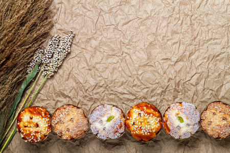 brown paper background: muffins with millet on brown paper background