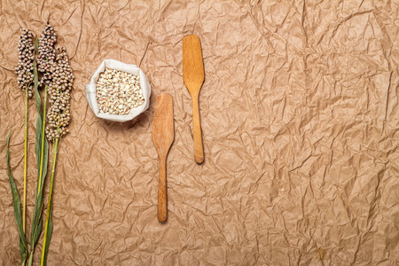 brown paper background: millet in sack on brown paper background Stock Photo