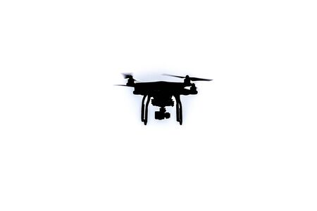 flying float: Black Drone hovering in a bright sky Stock Photo