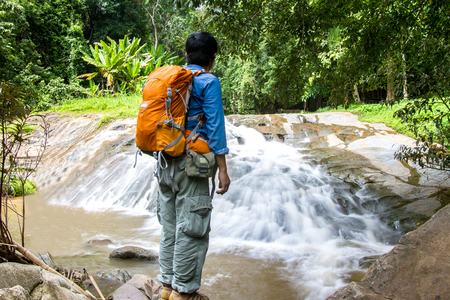 young man standing in front of waterfall with looking at waterfall and travel backpack in Thailand Stock Photo