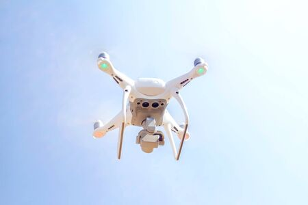 Drone copter flying with digital camera on the sky and sunlight background