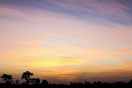 Sunrise with an orange and yellow sky and landscape background